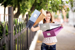 Young caucasian woman walking on the street with shopping bags. Stock Photography