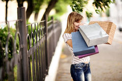 Young caucasian woman walking on the street with shopping bags. Royalty Free Stock Image