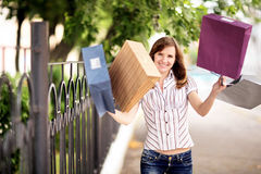 Young caucasian woman walking on the street with shopping bags. Royalty Free Stock Photos