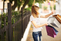 Young caucasian woman walking on the street with shopping bags. Royalty Free Stock Images