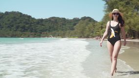 Young woman walks along sandy beach by sea stock footage