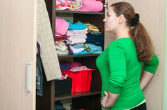 Young caucasian woman in the wardrobe selecting things. For wear Royalty Free Stock Images