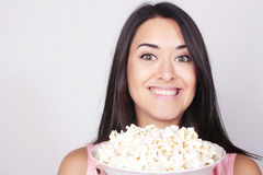 Young caucasian woman watching a movie / TV. While enjoying a snack. Girl eating popcorn. Leisure time Royalty Free Stock Image