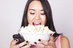 Young caucasian woman watching a movie / TV. While enjoying a snack. Girl eating popcorn and pointing the remote control to the camera Royalty Free Stock Images