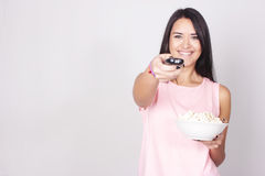 Young caucasian woman watching a movie / TV. While enjoying a snack. Girl eating popcorn and pointing the remote control to the camera Royalty Free Stock Image