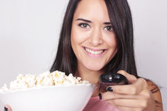 Young caucasian woman watching a movie / TV. While enjoying a snack. Girl eating popcorn and pointing the remote control to the camera Royalty Free Stock Photo