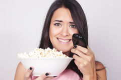 Young caucasian woman watching a movie / TV. While enjoying a snack. Girl eating popcorn with scared expression Royalty Free Stock Photos