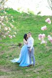 Young caucasian woman wearing blue dress and walking near magnolia with boyfriend. Young caucasian women wearing blue dress and walking near magnolia with royalty free stock image