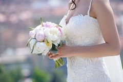 Young Caucasian woman wearing an embroidered wedding dress and holding a round peonies bouquet, an essential accessory for a bride. Horizontal shot of female Royalty Free Stock Photos