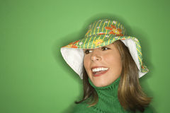 Young Caucasian woman wearing hat. Portrait of smiling young adult Caucasian woman on green background wearing floppy hat Stock Image