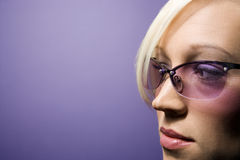 Young Caucasian woman wearing sunglasses. Close-up portrait of young adult Caucasian blond woman on purple background wearing sunglasses Stock Image