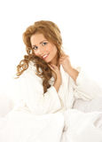 A young Caucasian woman in a white bathrobe Stock Image