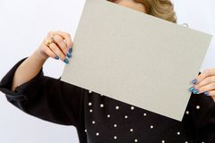 Young Caucasian woman on a white isolated background holding a sheet of cardboard without labels. stock image