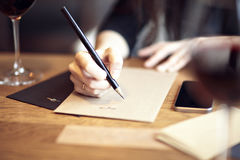 Young caucasian woman working, writing in a restaurant. Business concept. Stationary layouts Royalty Free Stock Images