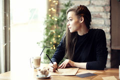 Young caucasian woman working, writing in a restaurant. Business royalty free stock image