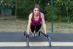 Young caucasian woman workouts on the park sports ground. In a sports plank position, bright sportswear. Young caucasian woman workouts on the park sports stock photo