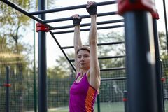 Young caucasian woman workouts on the park sports ground. Pulling up on the vertical bar, bright sportswear, protective gloves, vi stock photos