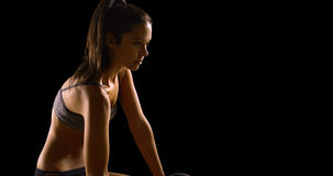 Young Caucasian woman works out on a black background with copy space Stock Photography