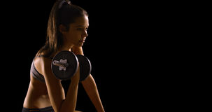Young Caucasian woman works out on a black background with copy space Stock Images