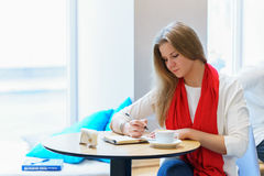 Young caucasian woman is writing some idea or letter in her note book, by pen. Close to cup of coffee Royalty Free Stock Photos