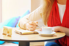 Young caucasian woman is writing some idea or letter in her note book, by pen. Close to cup of coffee Stock Image