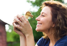 Young caucasian woman with yellow duckling Royalty Free Stock Photography