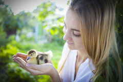 Young caucasian woman with yellow duckling outdoors Stock Photos