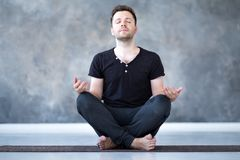 Yoga male beginner practicing yoga sitting in pose and meditates royalty free stock photography