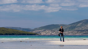 Young Caucassian woman enjoying holiday on a white sandy beach with turquoise water. Luskentyre, Isle of Harris, Scotland Stock Photos