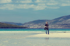 Young Caucassian woman enjoying holiday on a white sandy beach with turquoise water. Luskentyre, Isle of Harris, Scotland Royalty Free Stock Photo