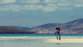 Young Caucassian woman enjoying holiday on a white sandy beach with turquoise water. Luskentyre, Isle of Harris, Scotland Stock Image