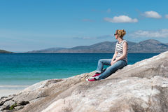 Young Caucassian woman enjoying holiday on a white sandy beach with turquoise water. Luskentyre, Isle of Harris, Scotland royalty free stock photos