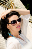 Young caucausian brunette laying in the hammock at ocean resort Royalty Free Stock Images