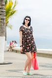 Young caucausian brunette with summer bag strolling on boardwalk Stock Photo
