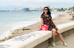 Young caucausian brunette with summer bag strolling on boardwalk Royalty Free Stock Images