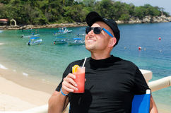 Young caucausian man enjoys coctail at ocean resort during  summ Royalty Free Stock Photography