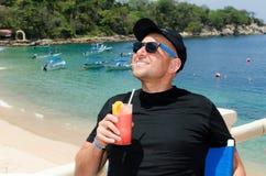 Young caucausian man enjoys coctail at ocean resort during  summ Royalty Free Stock Photography