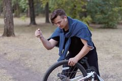 Young causacian man with screwdriver tries to damage the bicycle wire at the abandoned park. Vandal actions. royalty free stock photo