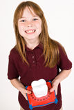 Young caucasion girl waiting on the tooth fairy. A young causation girl showing off her missing teeth. She holds a tooth holder piggy bank used while waiting on Royalty Free Stock Image