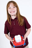 Young caucasion girl waiting on the tooth fairy. A young causation girl showing off her missing teeth. She holds a tooth holder piggy bank used while waiting on Royalty Free Stock Photography