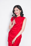 Young celebrating asian woman in red dress holding wine glass. stock image