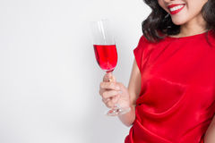 Young celebrating beautiful asian woman in red dress holding win. E glass Royalty Free Stock Photo