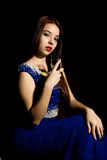 Young celebrating woman in a blue dress holding glass of champagne, dark background. play light and shedow Royalty Free Stock Photography
