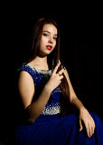 Young celebrating woman in a blue dress holding glass of champagne, dark background. play light and shedow Stock Photo