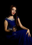 Young celebrating woman in a blue dress holding glass of champagne, dark background. play light and shedow Royalty Free Stock Photo