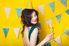 Young celebrating woman green dress, holding a glass of champagne. Stock Photo