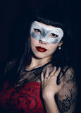 Young celebrating woman in a red dress, carnival mask on her face Royalty Free Stock Photography