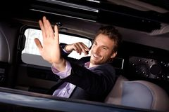 Young celebrity waving from limousine smiling Royalty Free Stock Photo