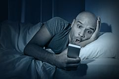 Young cell phone addict man awake at night in bed using smartphone Royalty Free Stock Photo