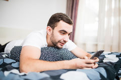 Young cell phone addict man awake at night in bed using smartphone for chatting, flirting and sending text message in internet add Stock Photography